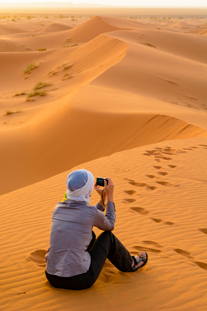 A woman is sitting on the sand dunes of Erg Chebbi and is photographing the Sahara sunrise. Merzouga, Morocco Reklamní fotografie