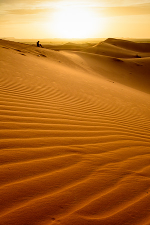 Sand lines at Erg Chebbi sand dune at sunrise. A woman is sitting on a sand dune in the distance. Sahara, Merzouga, Morocco