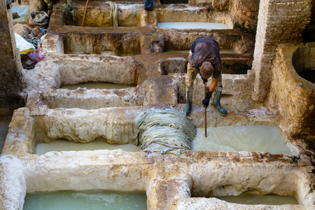 A worker tanning skin into leather in a tannery, Fez, Morocco Reklamní fotografie