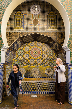 FEZ, MOROCCO - October 21 2013: A woman and young girl are drinking water from a public tap in Fez. The girl has filled in several empty plastic bottles.
