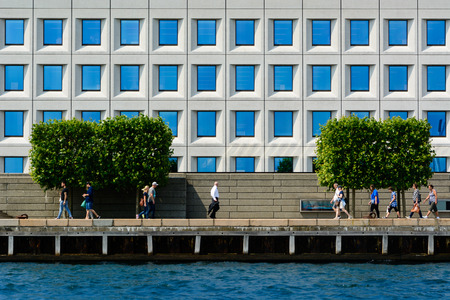 COPENHAGEN, DENMARK - JUNE 25 2016: People are walking in front of an office building located on the water front in Copenhagen.