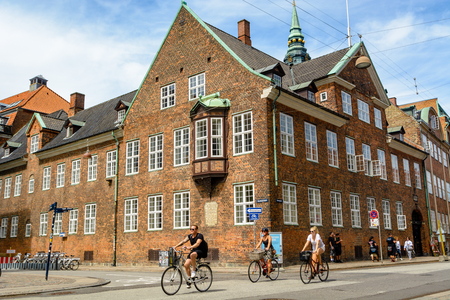 COPENHAGEN, DENMARK - June 24, 2016: Cyclists pedal on a street in Copenhagen. The building behind them represents typical Scandinavian architecture Redakční