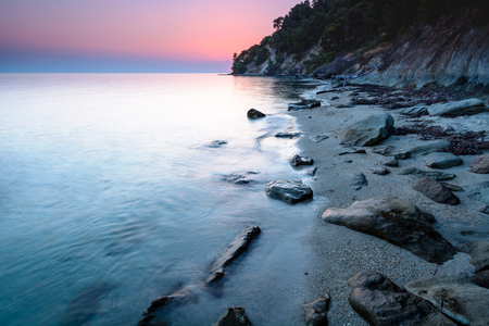 Long exposure of a dreamy and colorful sunset on a rocky beach in Chalkidiki, Greece