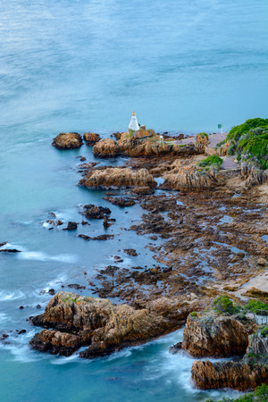 Long exposure with blurred water of a lighthouse on a rock at the entrance to the Knysna lagoon. Knysna is a popular stop along the Garden Route in South Africa
