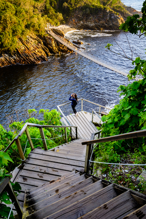 A woman looking through binoculars on a flight of stairs leading to the suspension bridge in Storms River Mouth national park in South Africa Reklamní fotografie