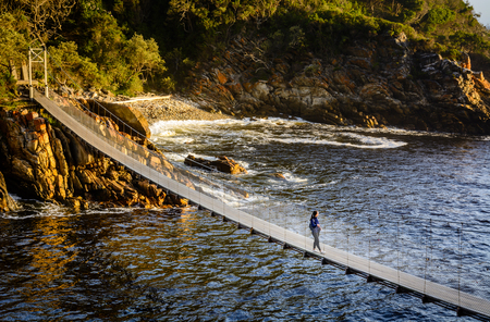 A girl is standing on the suspension bridge in Storms River Mouth national park in South Africa Reklamní fotografie