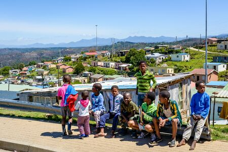 KNYSNA, SOUTH AFRICA - November 18, 2017: Children are sitting by the road in a township in Knysna near the government-subsidized Mandela houses
