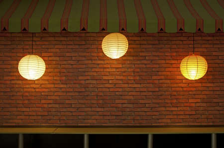 Brick wall with three illuminated lamps photo