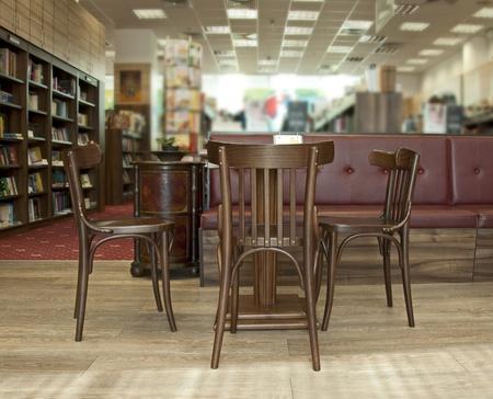 Bibliotheek met stoelen en tafel. Veel boeken Stockfoto