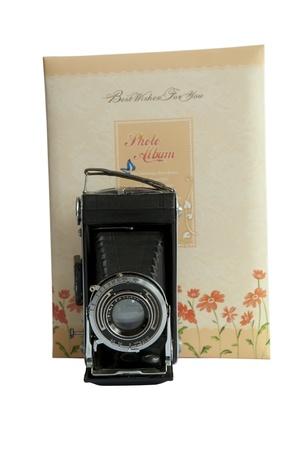 Photo album and vintage camera isolated on white photo