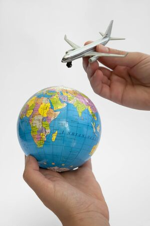 Globe and plane with two hands photo
