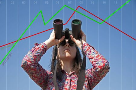 Young woman with binoculars and stock market scale photo