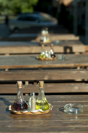 Wooden table in the restaurant and utensils. Vinegar and olive oil photo