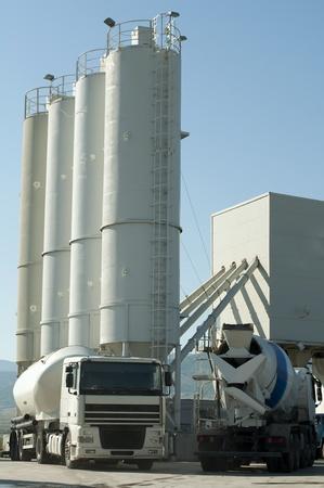 Cementfabriek en twee witte vrachtwagens laden cement Stockfoto
