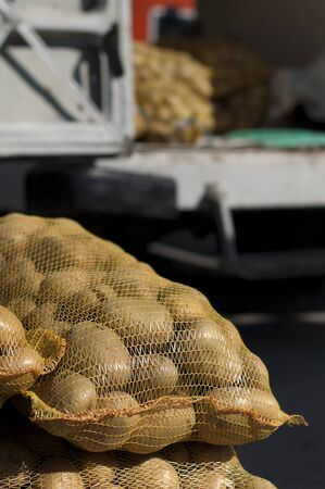 Potatoes in mesh bags in Wholesale market. Blurred track on background photo