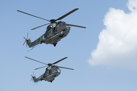 Two green military helicopters on blue sky background