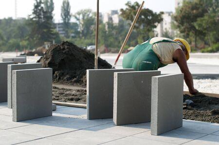 A worker puts exterior tiles