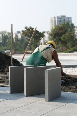 A worker puts exterior tiles  Stock Photo - 10678116