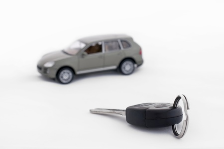 Car keys and a car in the background. White isolates photo