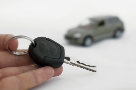 new entry: Hand holding keys and a car in the background. White isolates Stock Photo