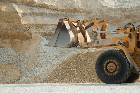 Bulldozer in quarry. Huge pile of limestone and sand photo