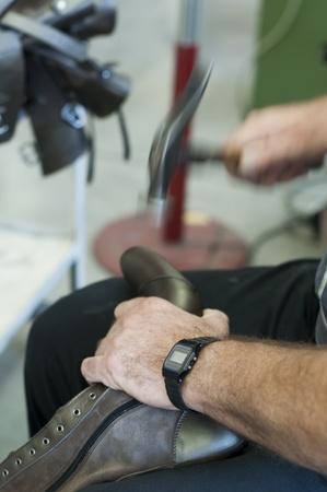 Handgemaakte vervaardiging van schoeisel. Hameren met een hamer