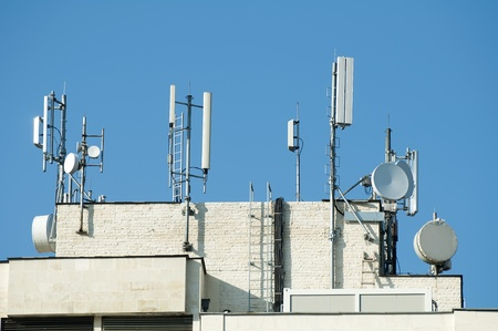 intercommunication: GSM transmitters on a roof of white administrative building. Close up Stock Photo