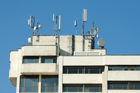 GSM transmitters on a roof of white administrative building Stock Photo