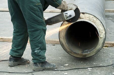 Cutting of pipes with grinder. Hot water and steam heating pipe photo
