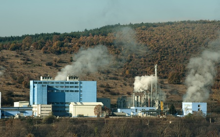 Industrial factory with chimneys and smoke in the forest