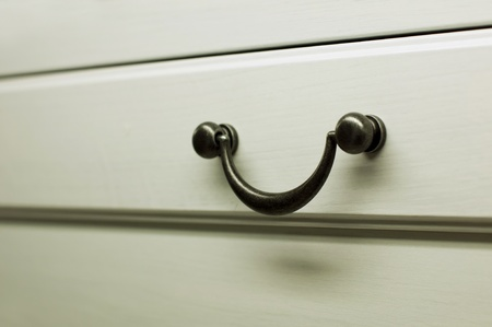 Kitchen cabinet handles. White colored wood photo
