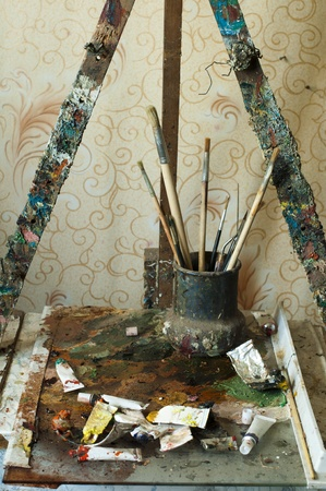 Easel for painting, tubes of oil paint and brushes. Artistic studio photo
