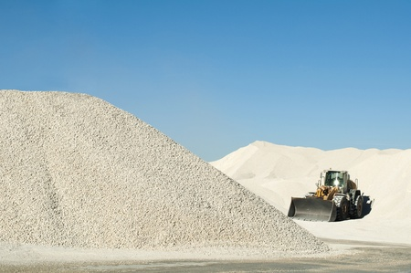 Graafmachine in een kalkstenen quarry.Piles van kalksteen rotsen
