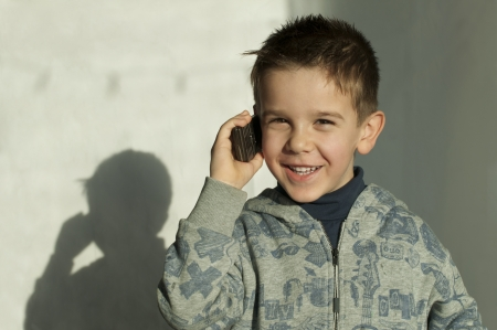 Smiling child talking by mobile phone photo