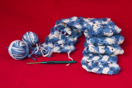Ball of yarn and knitting skewers. Blue and white color scarf on red background photo