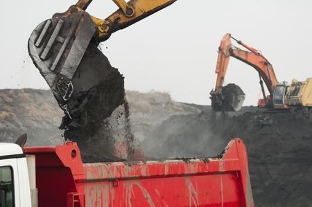 dumper truck: Excavator loading truck. White isolated Editorial