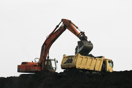 Excavator loading truck. White isolated