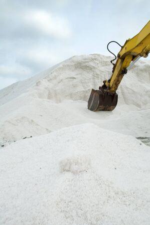 Excavator digging pile white salt photo