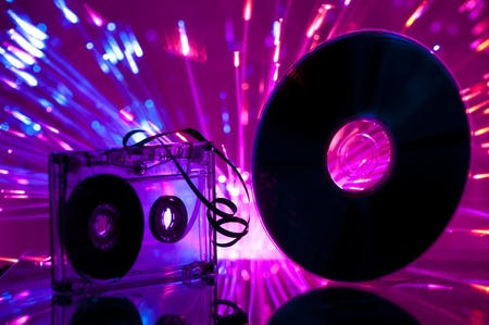 Cassette tape and CD. Multicolored blue lights on background Imagens