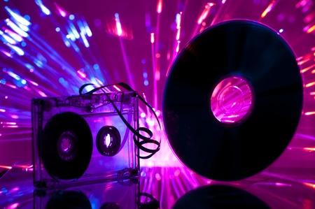 Cassette tape and CD. Multicolored blue lights on background Standard-Bild