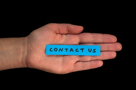 correspond: Word Contact us on blue paper and hand Stock Photo