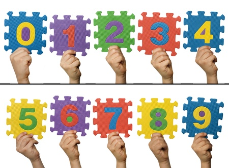 Children hands holding numbers. White isolated multicolor numbers. photo