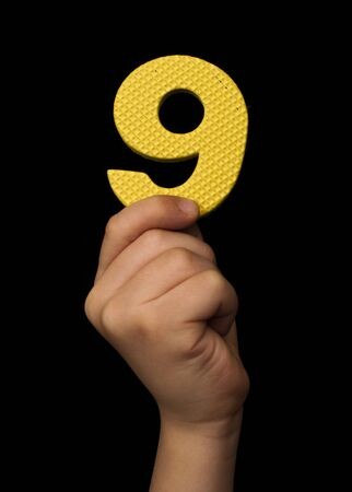 Children hand holding the number Nine. Black isolated yellow color number Nine
