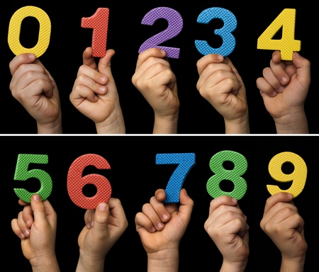 Children hands holding numbers. Black isolated multicolor numbers. photo