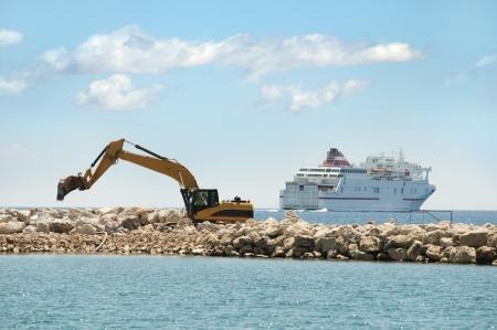 Het bouwen van een dijk. Graafmachine zet stenen in de zee. Een schip op de achtergrond Stockfoto