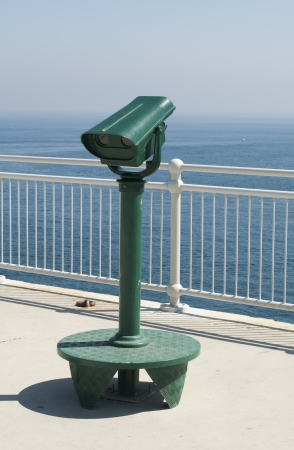 lookout: Green tourist telescope. Sea view and sky