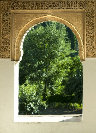 Islamic motifs arch window and green garden outside photo
