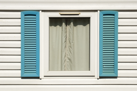 Window with blue wooden shutters. White wall Stock Photo - 15818185