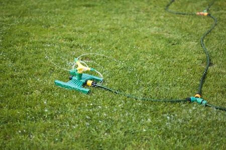 Lawn sprinkler splashing water over green grass. photo