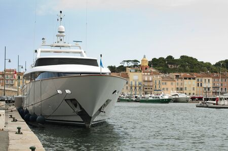 southern european: Anchored Yacht in St. Tropez. Ancient buildings on the background. Stock Photo